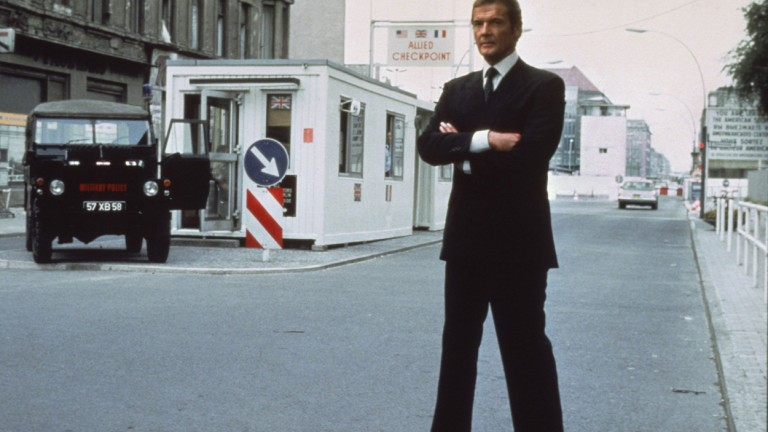 Roger Moore at Checkpoint Charlie border crossing in 1982 - Photo: EON Productions, Danjaq